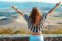 Réjouissance moderne de femme de voyageur contre le paysage de la Toscane image stock