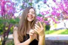 Réjouissez la fille à l'aide du smartphone dans le parc avec le fond de fleur Photos libres de droits