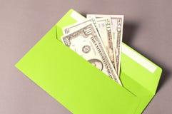Rémunérez dans l'enveloppe verte avec l'argent sur le fond gris Images libres de droits