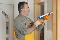 Rénovation à la maison, calfeutrant la porte avec du silicone image stock