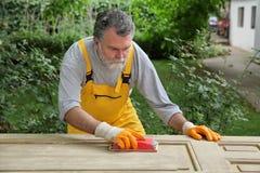 Rénovation à la maison, travailleur ponçant la porte en bois Photos libres de droits