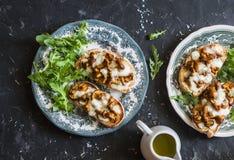 Répand le tartine Sandwichs cuits au four avec les chanterelles et le mozzarella de champignons sur un fond foncé photo stock