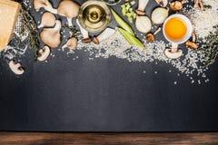 Répand les ingrédients de risotto sur le fond noir de tableau, vue supérieure photo libre de droits