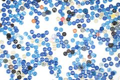 Répandez les petits boutons de couture bleus sur un fond blanc Photos libres de droits