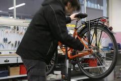 Réparant la bicyclette à l'intérieur de l'atelier mécanique se spécialisant dedans Photos stock