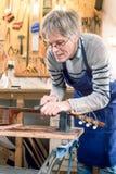 Réparateur de guitare classant les frettes d'une guitare acoustique Image stock