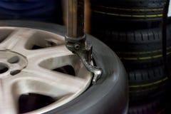 Réparateur de PNEU réparant un pneu Photos stock