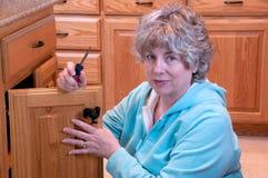 Réparation à la maison faisante femelle aînée photographie stock libre de droits