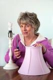 Réparation à la maison faisante femelle aînée - lampe photographie stock libre de droits