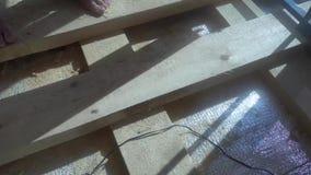 Réparation, bâtiment, plancher et concept de personnes - fermez-vous de l'homme installant le plancher en bois banque de vidéos