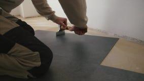 Réparation, bâtiment, plancher et concept de personnes - fermez-vous de l'homme installant le plancher banque de vidéos