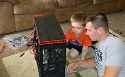 Réparation d'ordinateur de père et de fils Photographie stock