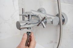 Réparation d'un robinet dans une salle de bains Image libre de droits