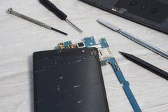 Réparation d'un téléphone portable, smartphone Les outils spéciaux se trouvent sur la partie supérieure du comptoir avec les élém photo stock