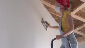 Réparation dans l'appartement - une jeune femme d'aspect européen dépanne à la maison - polissage extérieur de mur banque de vidéos