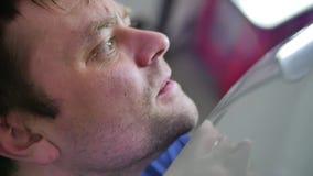 Réparation de bosselure de Paintless Fermez-vous du visage intensément attentif d'un artisan qui répare une voiture sans peinture banque de vidéos