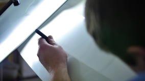 Réparation de bosselure de Paintless Maître en gros plan qui répare le capot d'une automobile de couleur argent dans un atelier d banque de vidéos