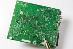 Réparation de carte système électronique avec le fer à souder photographie stock