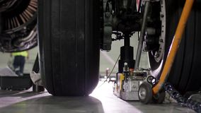 Réparation de frein d'avions Fermez-vous de la roue et de l'axe d'avion Pneu énorme d'avion avec l'axe et le train d'atterrissage banque de vidéos