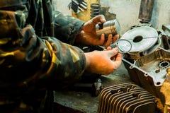Réparation de moteur de moto dans le garage Photographie stock libre de droits