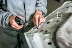 Réparation de voiture dans le service de voiture Détail de voiture de morcellements de serrurier, plan rapproché de mains image stock