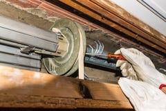 Réparation de volet de roulement Le travailleur ajuste un volet cassé de rouleau d'une maison photo stock
