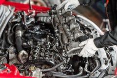 Réparation du moteur diesel, des mains de travailleurs et de l'outil modernes Mécanicien de voiture regardant le moteur pour des  image stock