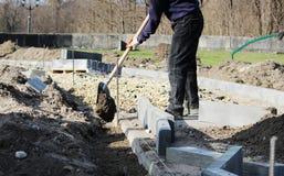 Réparation du trottoir Le tailleur de pierres travaillant réparent le trottoir, installent des restrictions avant pour la route a Image stock