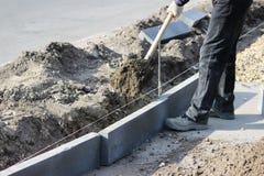 Réparation du trottoir Le tailleur de pierres travaillant réparent le trottoir, installent des restrictions avant pour la route a Photographie stock libre de droits