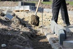 Réparation du trottoir Le tailleur de pierres travaillant réparent le trottoir, installent des restrictions avant pour la route a Photos libres de droits