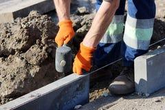 Réparation du trottoir Les maçons travaillants professionnels dans des combinaisons transmettent des restrictions à étendre les p Photographie stock