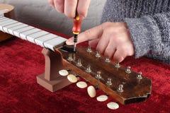 Réparation et service de guitare - le travailleur règle une tige de botte de guitare photographie stock