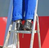 réparation Les pieds du travailleur dans un uniforme sur une étape-échelle Photos libres de droits