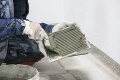 réparations Pose des carreaux de céramique de plancher Mains du ` s d'hommes dans les gants avec la spatule, mortier répandu de c Photo libre de droits