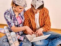 Réparez la famille par la maison heureuse de bâtiment de couples utilisant l'ordinateur portable blanc Images stock