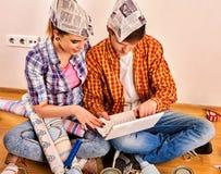 Réparez la famille par la maison heureuse de bâtiment de couples utilisant l'ordinateur portable blanc Photo stock