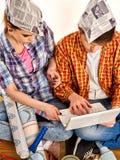 Réparez la famille par la maison heureuse de bâtiment de couples utilisant l'ordinateur portable blanc Images libres de droits
