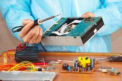 Réparez le matériel électronique avec un fer à souder dans l'atelier de service Photographie stock libre de droits