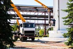 Réparez les colonnes sur une technique spéciale Les travailleurs sur la grue réparent une grande colonne blanche Réparation cosmé photos stock