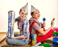 Réparez les femmes à la maison tenant le rouleau d'outils de peinture pour le papier peint Image libre de droits