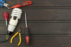 Réparez les lumières cassées Ampoule économiseuse d'énergie sur un fond foncé Ventes des ampoules La publicité sur la technologie Image libre de droits