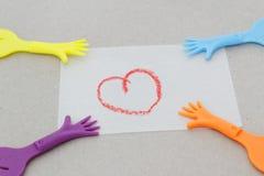 Réplica da mão que puxa o papel com símbolo do amor Fotos de Stock Royalty Free