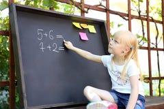 Réponse mignonne d'écriture de petite fille à la craie exerciseusing sur le tableau noir Photo stock