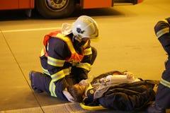 RÉPUBLIQUE TCHÈQUE, PLZEN, LE 30 SEPTEMBRE 2015 : Le sapeur-pompier courageux soulagent blessé après accident de voiture Photos libres de droits