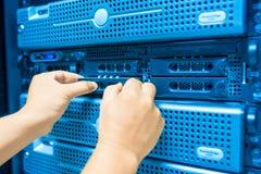 Réseau de serveur de difficulté d'homme dans la chambre de centre de traitement des données photographie stock libre de droits