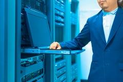 Réseau de serveur de difficulté d'homme dans la chambre de centre de traitement des données photos stock