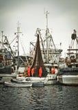 Réseaux de fixation d'équipage de pêcheur sur le bateau de pêche Image libre de droits