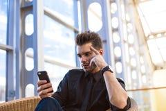 Réservation en ligne d'homme d'affaires sûr par l'intermédiaire du téléphone portable, se reposant dans le hall d'entreprise photos stock