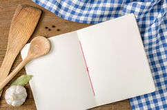 Réservez avec les cuillères en bois sur une nappe à carreaux bleue Photographie stock libre de droits