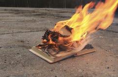 Réservez avec les pages brûlantes sur une surface en béton photos libres de droits